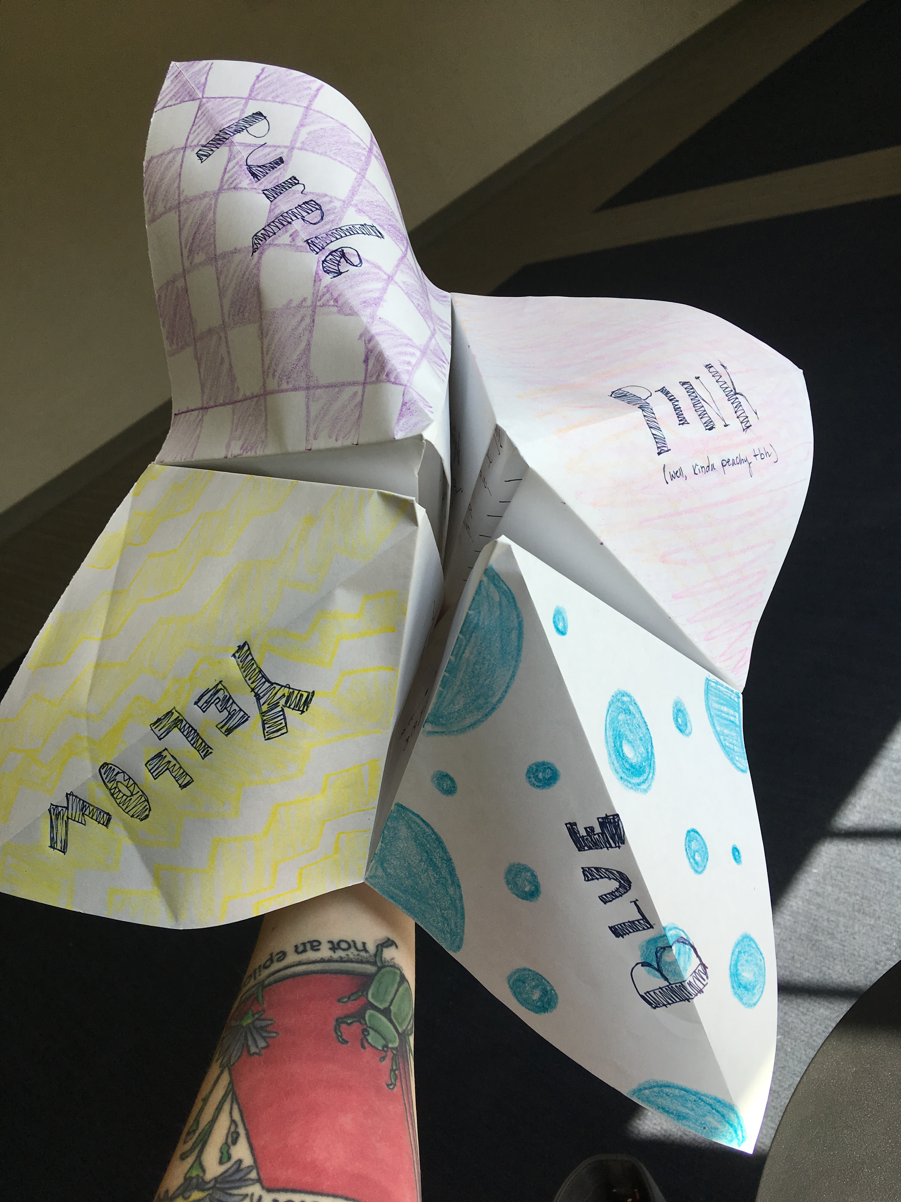 A very large cootie catcher with blue, yellow, purple, and pink written on its sections, over patterns of the same colors.